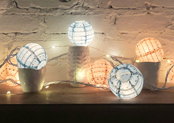Unique gender reveal idea using string lights with paper globes // www.thehiveblog.com